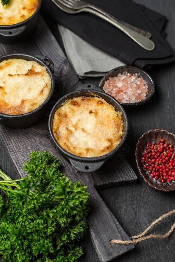 Пирог чабана, великобританский сотейник в лотке литого железа, с семенить мясом, картофельными пюре и овощами, на темной предпосы стоковое изображение