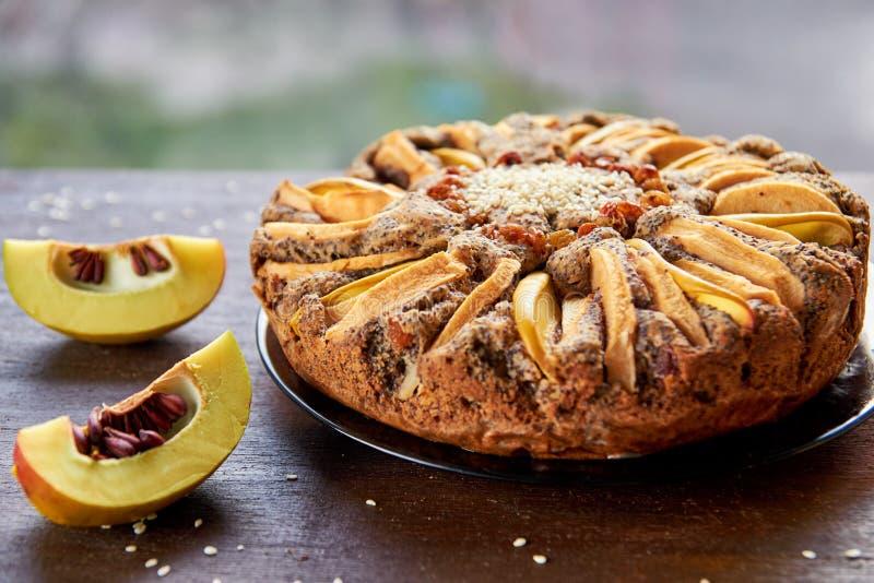 Пирог Яблока с айвой, маковыми семененами, изюминками и сезамом на деревянной коричневой таблице Яблочный пирог украшенный с отре стоковое фото