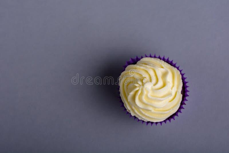 Пирожное в пурпурном обруче на голубой предпосылке Минималистский взгляд сверху с космосом экземпляра стоковое фото