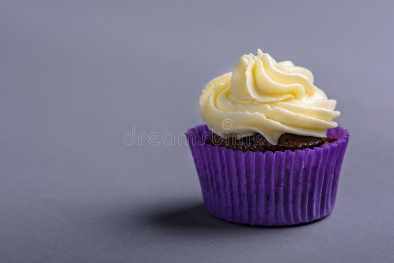 Пирожное в пурпурном обруче на голубой предпосылке Минималистский космос экземпляра стоковые фото