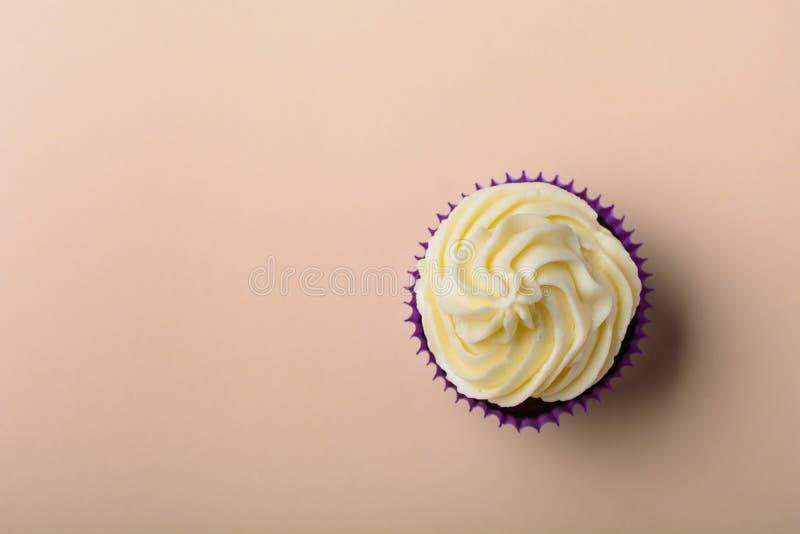 Пирожное в пурпурном обруче на предпосылке пастельного цвета персика minimalism r стоковые изображения