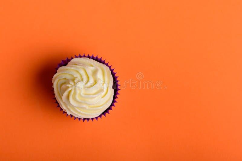 Пирожное в пурпурном обруче на предпосылке цвета коралла Минимальный r стоковая фотография