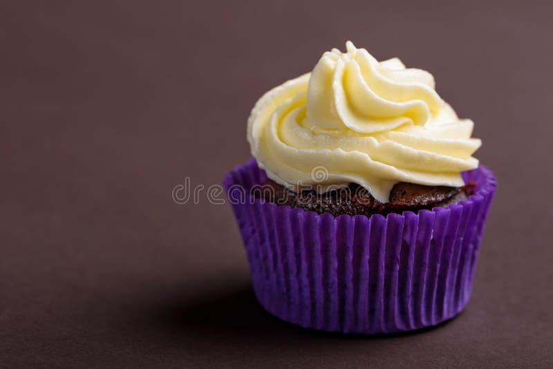 Пирожное в пурпурном обруче на темной коричневой предпосылке Минималистский космос экземпляра стоковое изображение rf