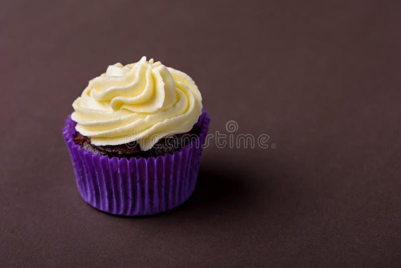 Пирожное в пурпурном обруче на темной коричневой предпосылке Минималистский космос экземпляра стоковая фотография