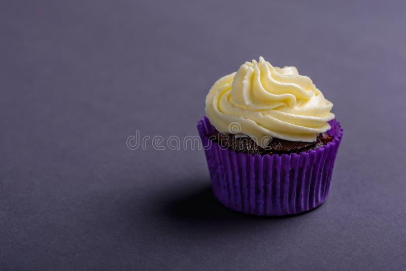 Пирожное в пурпурном обруче на темно-синей предпосылке Минималистский космос экземпляра стоковая фотография