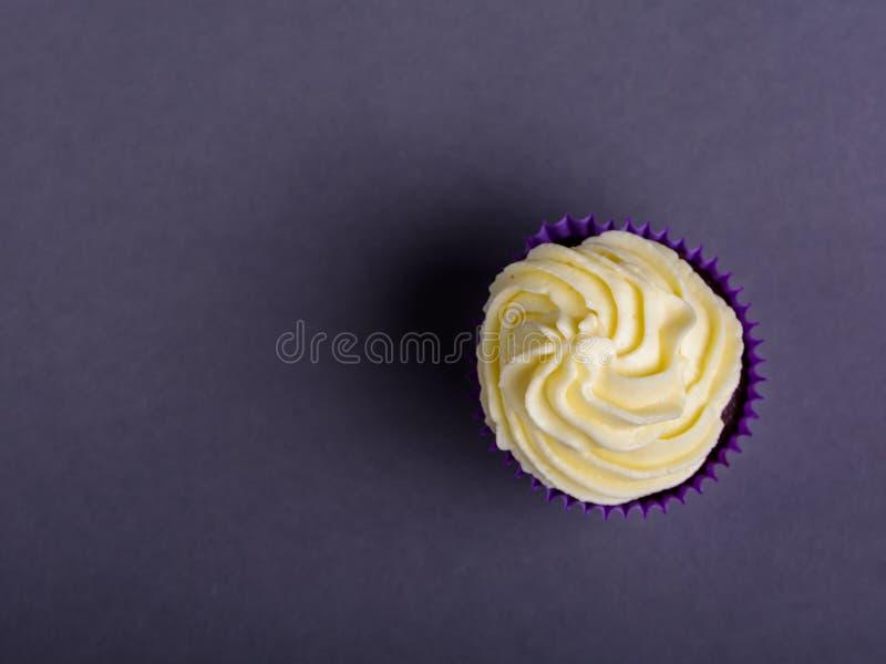 Пирожное в пурпурном обруче на темно-синей предпосылке Минималистский взгляд сверху с космосом экземпляра стоковое фото rf