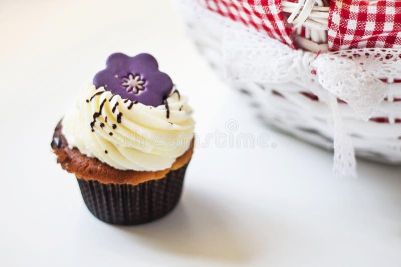 Пирожное с фиолетовым цветком на белой таблице стоковые изображения rf
