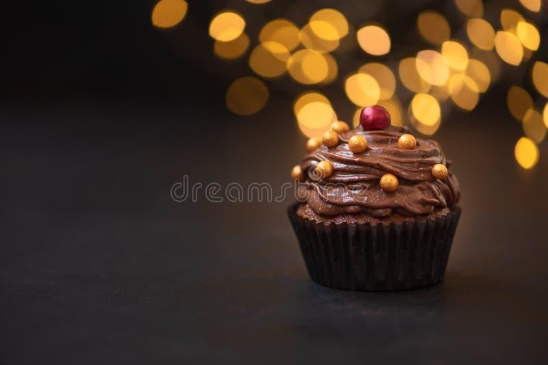 Пирожное шоколада с золотыми конфетами на темной деревянной предпосылке против запачканных светов r Нездоровая еда стоковое изображение rf