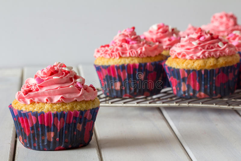 Пирожные и розовый замораживать на шкафе выпечки с одним концом вверх стоковое изображение rf