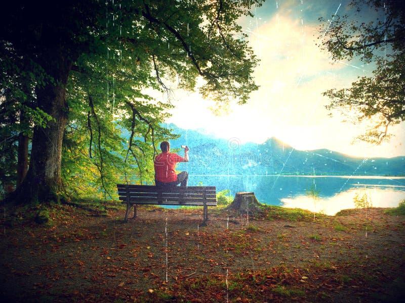 Пирофакел, мягкий фокус Человек сидит на деревянной скамье на озере горы Банк под деревом буков стоковые изображения