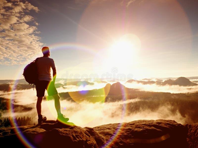 пирофакел Дефект объектива, отражения Hiker волос имбиря в черных брюках на скале над глубокой долиной стоковые фото