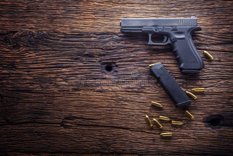 Пистолет оружия оружие и пули пистолета 9 mm посыпанные на деревенской таблице дуба стоковые изображения rf