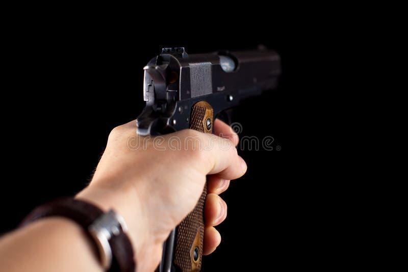 Пистолет 1911 в руке на черноте стоковое изображение rf