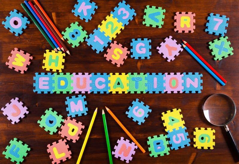 Письма головоломки с карандашами на деревянной предпосылке стоковые фотографии rf