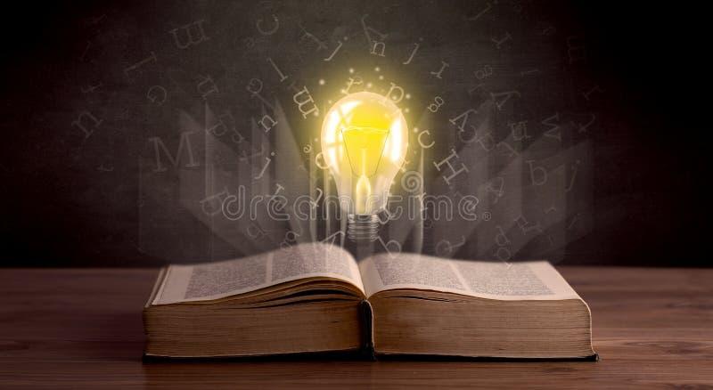 Письма и лампочка над книгой стоковая фотография rf