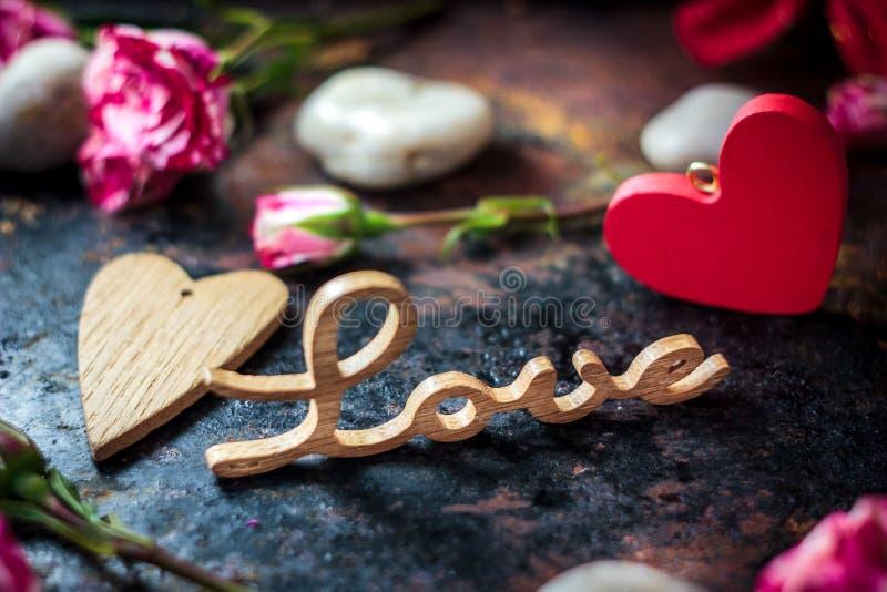 Письма ЛЮБЯТ на деревенской предпосылке с сердцами и цветками стоковое изображение