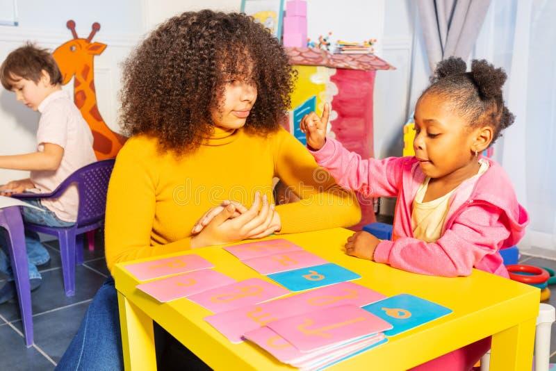 Письмо пункта девушки cursive учит с тактильными картами стоковая фотография