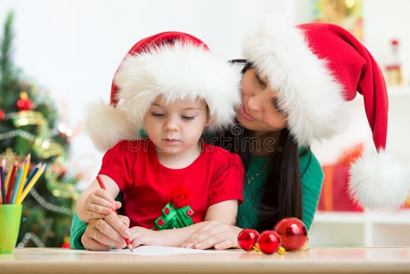 Письмо рождества сочинительства ребенка и матери к Санта Клаусу стоковое фото rf