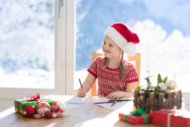 Письмо сочинительства ребенка к Санта на Рожденственской ночи Дети пишут Xmas присутствующую маленькую девочку списка целей сидя  стоковое изображение rf