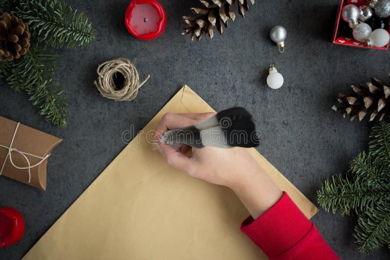 Письмо сочинительства девушки к Санте с ручкой чернил на желтой бумаге на серой предпосылке с украшениями рождества стоковые изображения