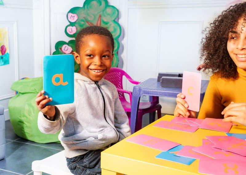 Письмо шоу мальчика cursive учит с тактильными картами стоковые фотографии rf