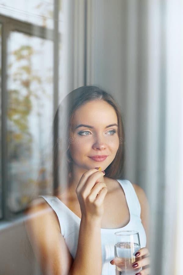 Питание здорового питания Портрет красивой молодой женщины принимая таблетку витамина смотря в окнах стоковое фото