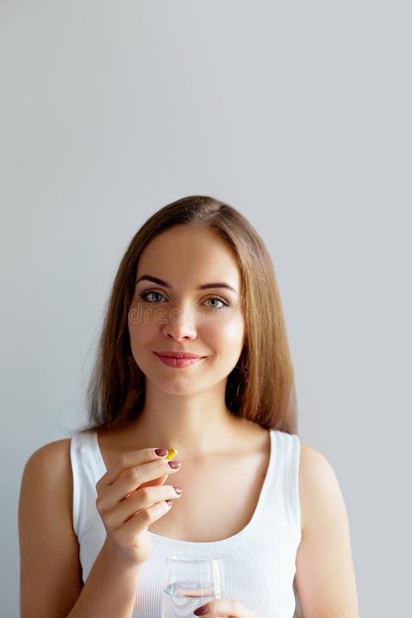 Питание здорового питания Портрет красивой усмехаясь молодой женщины принимая таблетку витамина Крупный план счастливой девушки д стоковые изображения