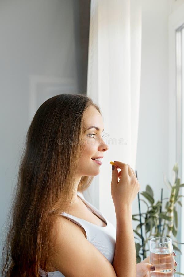 Питание здорового питания Портрет красивой усмехаясь молодой женщины принимая таблетку витамина стоковая фотография