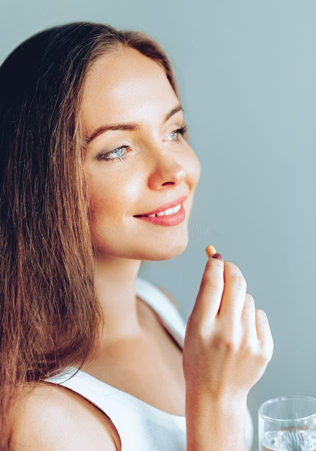 Питание здорового питания Портрет красивой усмехаясь молодой женщины принимая таблетку витамина стоковое изображение rf