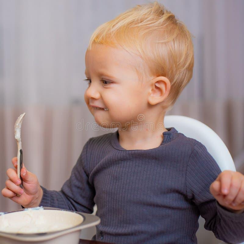 Питание младенца завтрака еды младенца мальчика милое o Малыш имея закуску дома Ребенок ест кашу Ребенк милый стоковые фото