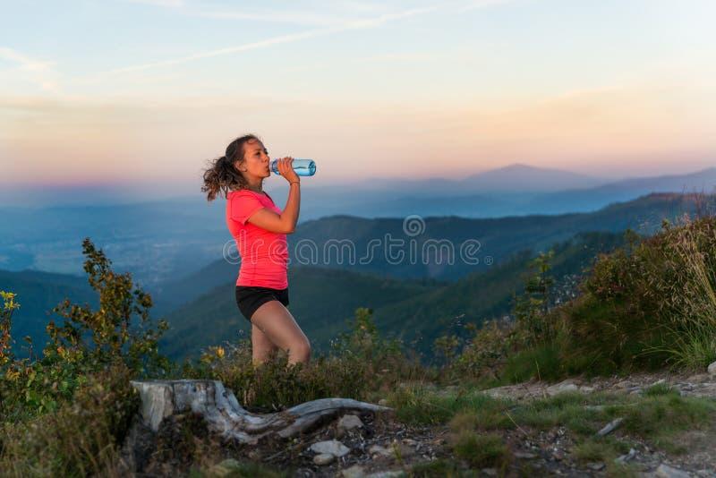 Питьевая вода бегуна по пересеченной местностей женщины в горах на лете стоковое изображение rf