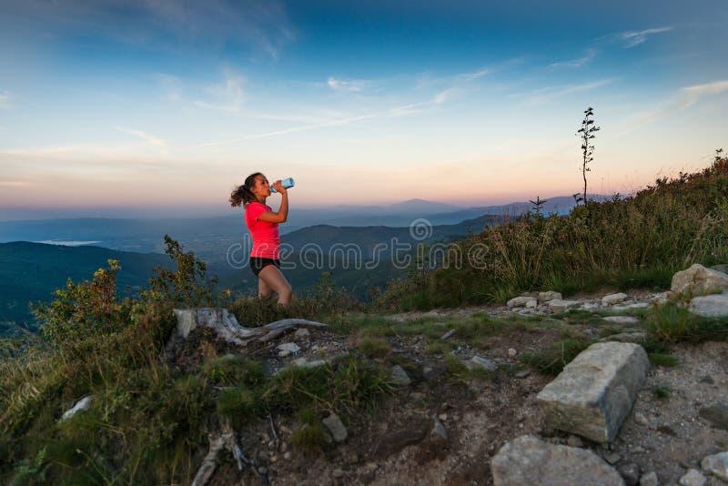 Питьевая вода бегуна по пересеченной местностей женщины в горах на лете стоковое фото