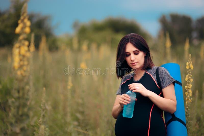 Питьевая вода беременной женщины после встречи йоги Outdoors стоковые изображения