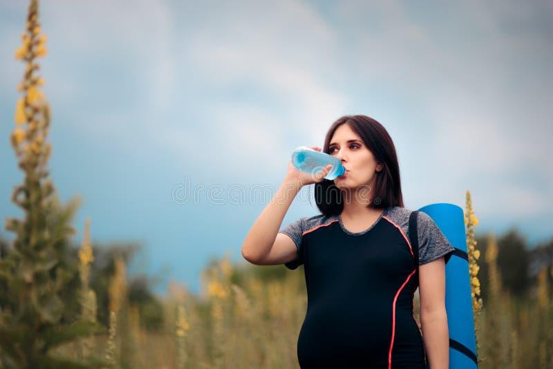 Питьевая вода беременной женщины после встречи йоги Outdoors стоковое изображение rf