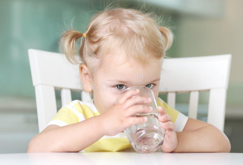 Питьевая вода девушки ребенка от стеклянного портрета крупного плана стоковые фотографии rf