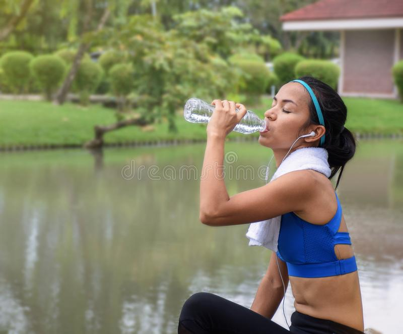 Питьевая вода женщины фитнеса от бутылки во время концепции образа жизни идущего спорта здоровой с космосом экземпляра стоковая фотография