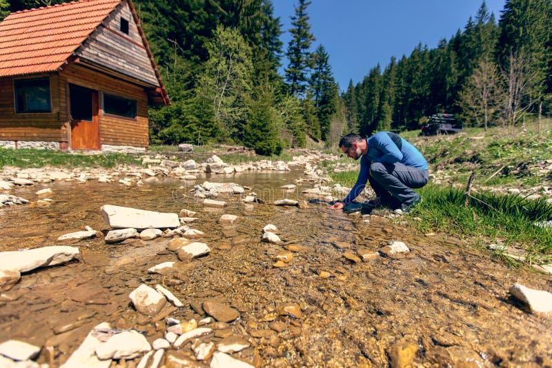 Питьевая вода молодого человека от весны стоковые изображения