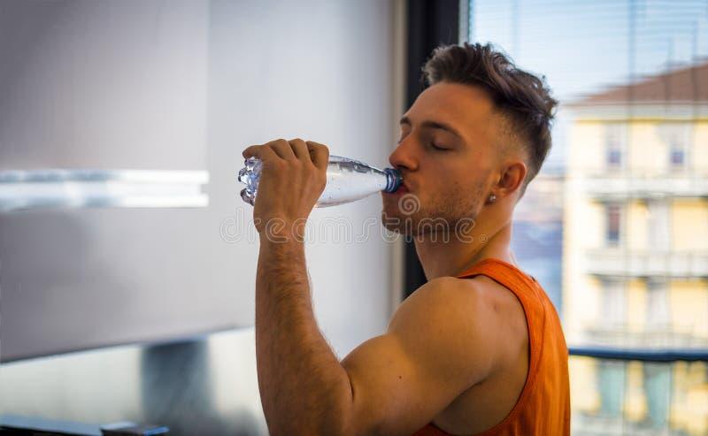 Питьевая вода молодого человека от пластиковой бутылки, стоковое изображение