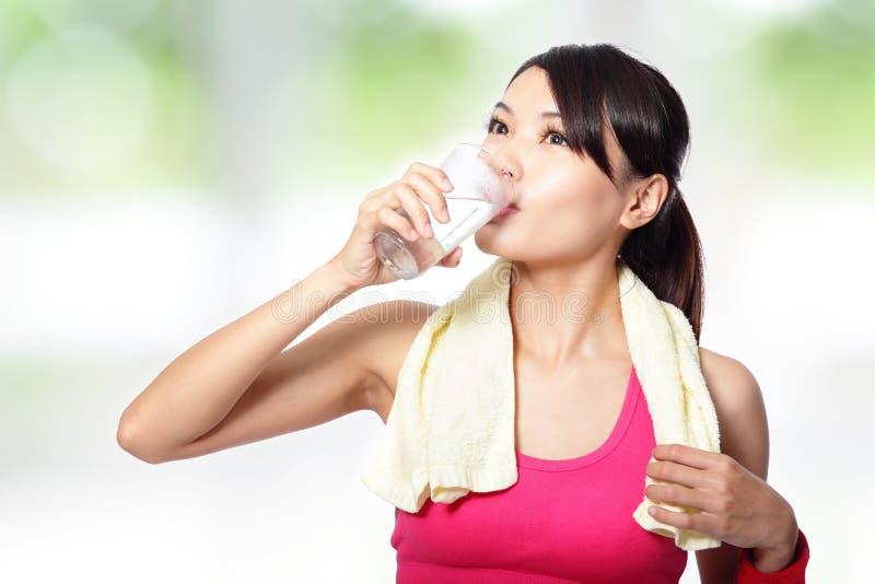 Питьевая вода молодой женщины после резвиться стоковое фото