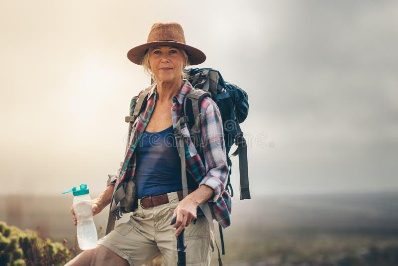 Питьевая вода hiker женщины во время ее трека стоковое изображение