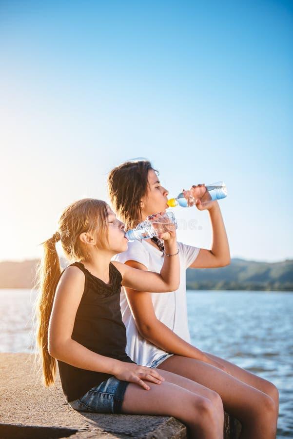 Питьевая вода 2 девушек и сидеть морем стоковые фото