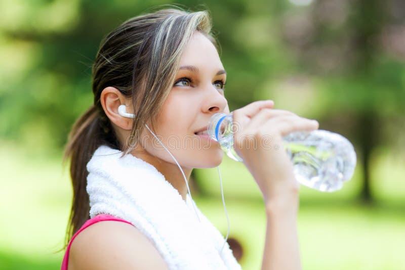 Питьевая вода женщины после бежать стоковая фотография