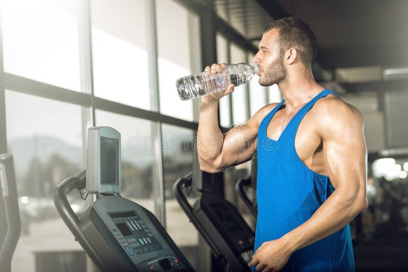 Питьевая вода молодого человека в спортзале стоковые изображения