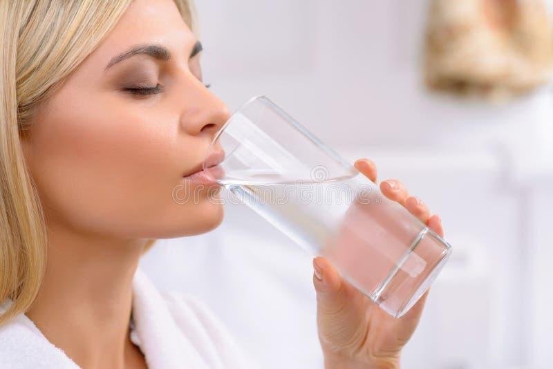 Питьевая вода молодой дамы стоковое фото