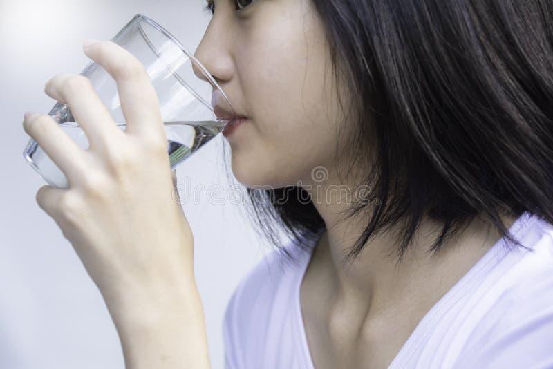 Питьевая вода молодой женщины Усмехаясь женское держа стекло стоковое фото rf