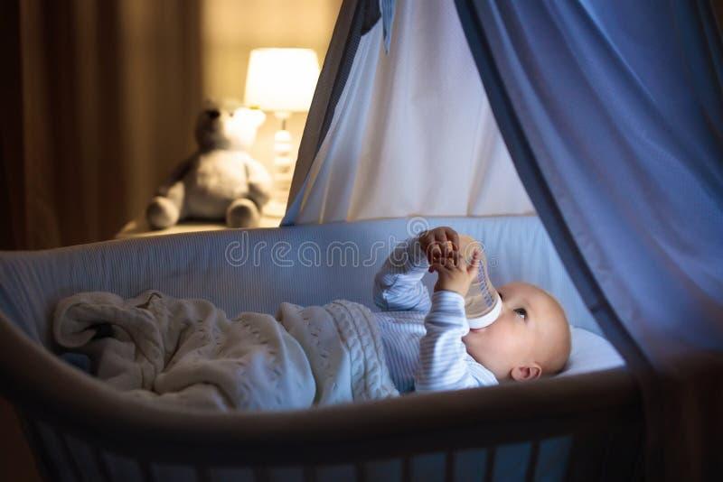 Питьевое молоко ребёнка в кровати стоковое изображение rf