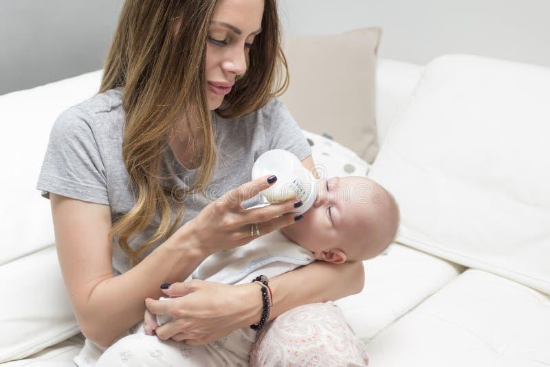 Питьевое молоко младенца от бутылки стоковые изображения rf