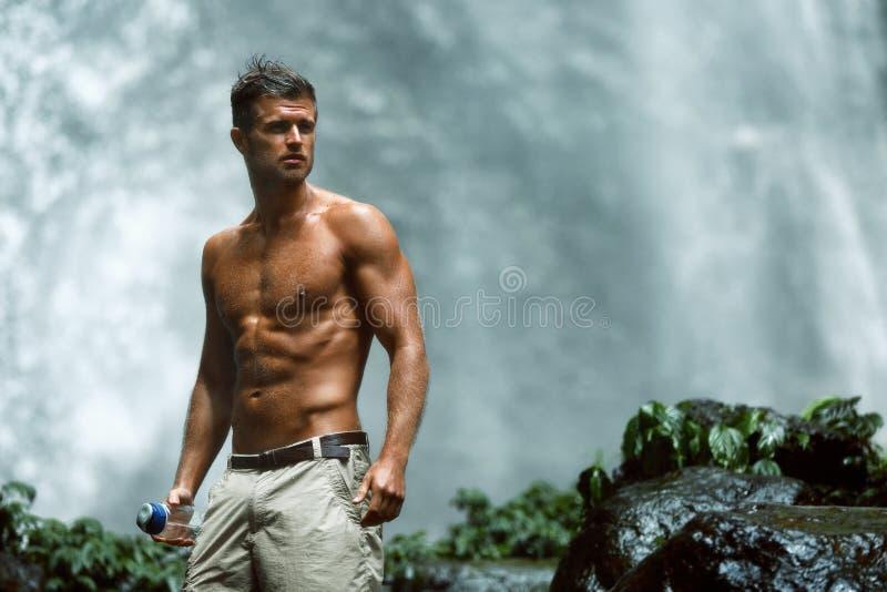 Питье воды Здоровый человек с сексуальным телом около водопада здоровье стоковые изображения