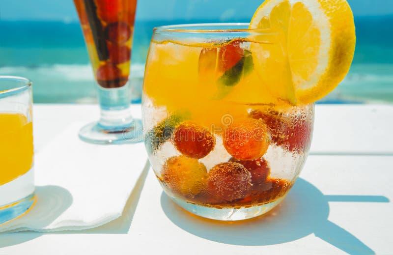 Питье коктеиля на деревянной таблице на предпосылке неба Охладите вне и концепция летнего отпуска стоковая фотография