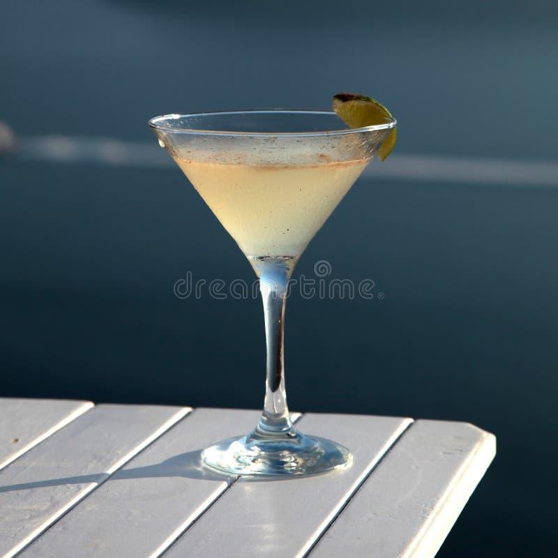 Питье коктеиля на деревянной таблице перед предпосылкой моря лета стоковые изображения rf